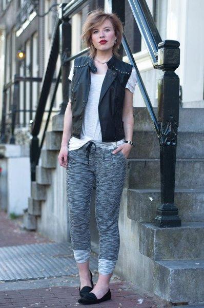 svart läderväst med nitar och grå stickade byxor