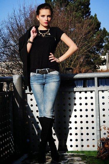 svart t-shirt med knäppt bälte och knähöga stövlar