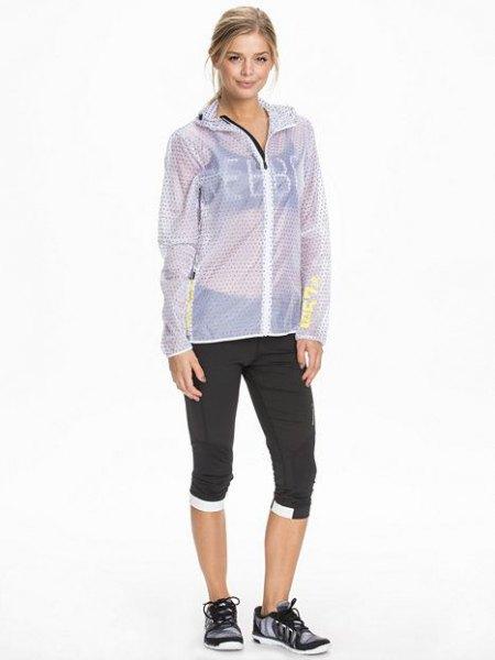blågrön, halvgenomskinlig jacka med svart sport-BH och beskurna joggebyxor