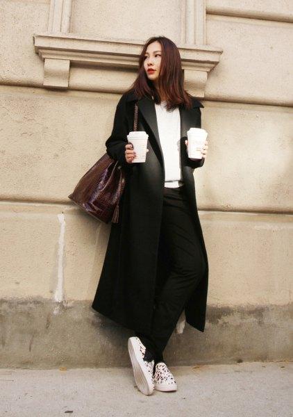 svart longline-kavajjacka med vit V-ringad tröja och sneakers i canvas