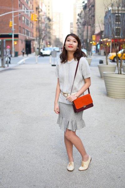 Elfenben kortärmad tröja med en grå frillad minikjol och vita oxfordläderskor