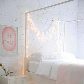 Använd strängljus för att öka intresset för vita sovrumsväggar.