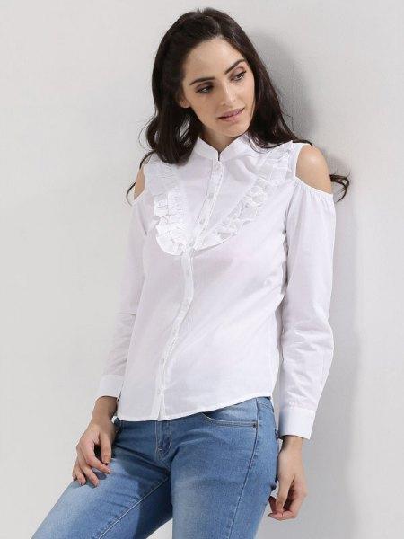 vit skjorta med volanger framtill och ljusblå skinny jeans