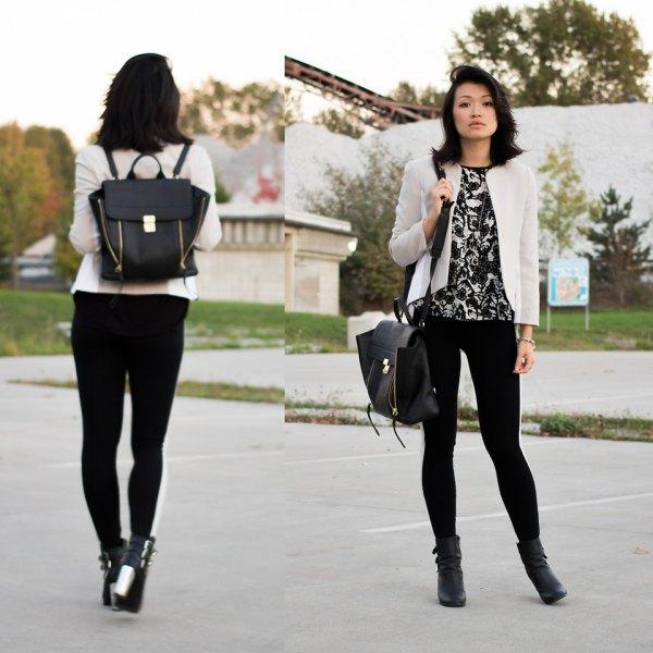 vit kavaj med svart tryckt t-shirt och läderhandväska
