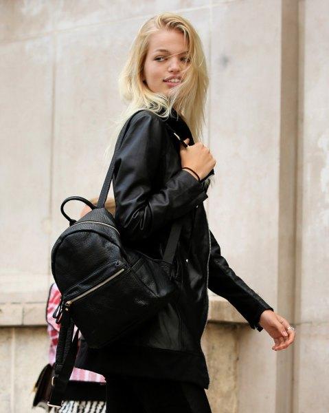 svart bomberjacka med ryggsäck och smala jeans