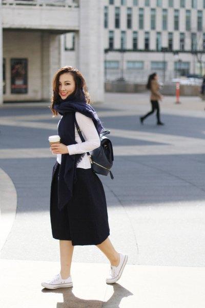 vit långärmad topp med svart utsvängd midikjol och ryggsäckplånbok