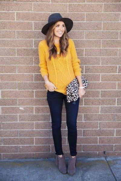 gul stickad tröja med svart filthatt