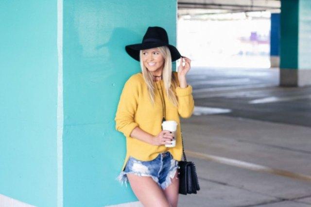 gul tröja med blå minishorts i rippad denim och floppy hatt