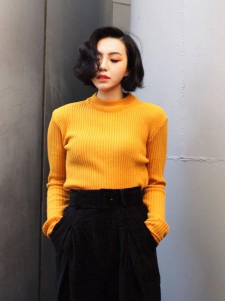 Ribbad gul tröja med svarta, beskurna byxor