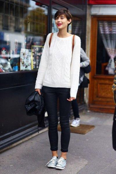 vit kabelstickad tröja med blå smala jeans med muddar