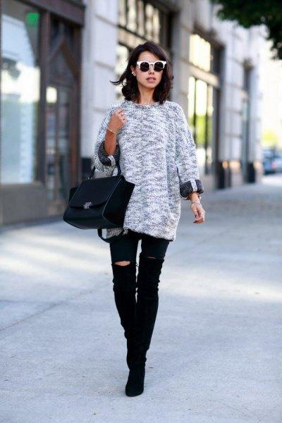 ljunggrå stickad tröja med svarta, rippade knäjeans