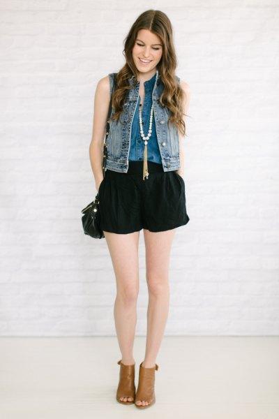 Jeansväst med svarta, flytande jeansshorts och öppna tåstövlar