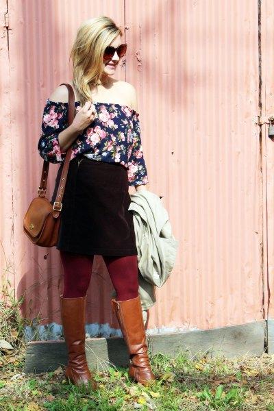 Svart och vit blus utan axel med blommönster, svart kjol och bruna stövlar