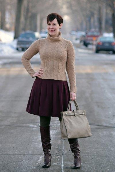 Figurkramande grön turtleneck med svart veckad kjol och bruna tights