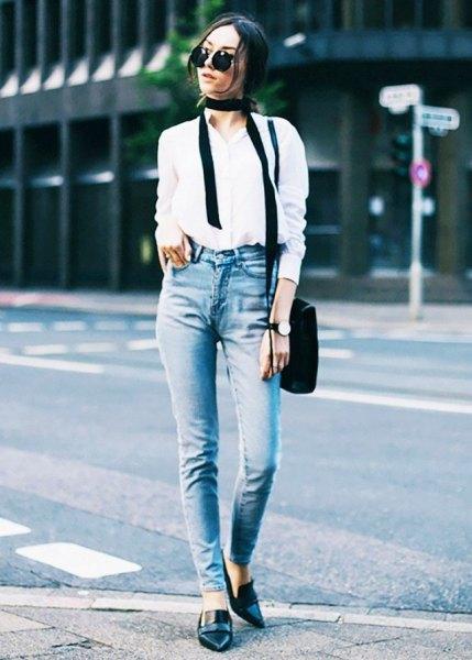 vit skjorta med knappar, jeans i smal passform och tofflor i svart läder med spetsiga tår