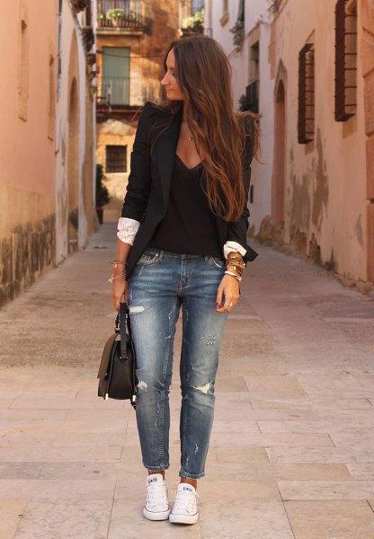 svart kavaj med djup V-ringad blus och blå rippade jeans