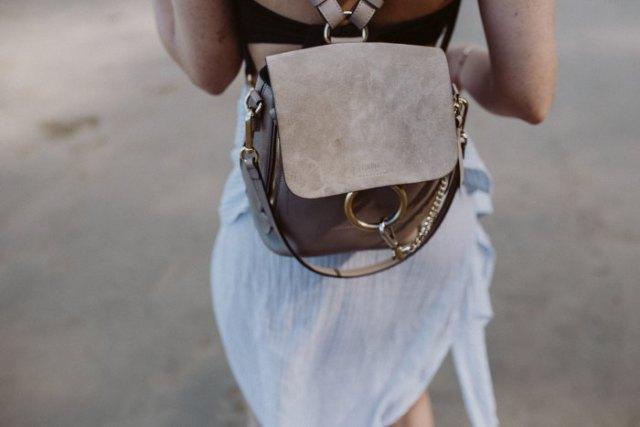 Luftig miniklänning i vit chiffong med en grå ryggsäckhandväska