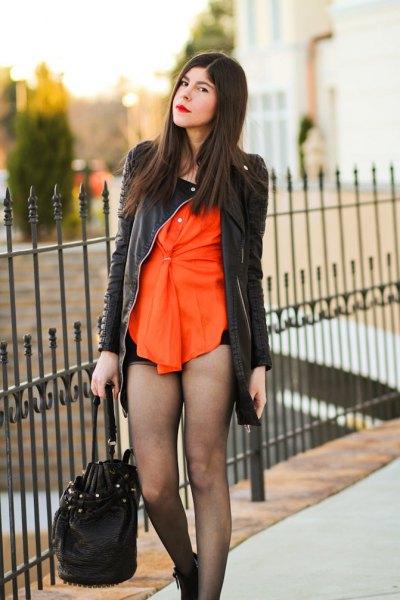 svart skinnjacka med orange blus och mini-shorts