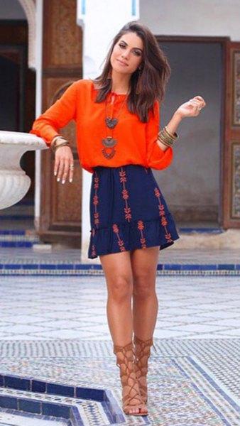 orange blus med rund halsringning och blå minirater kjol