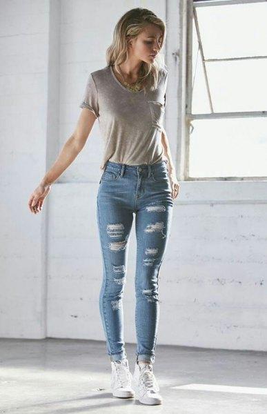 grå t-shirt med blå skinny jeans med muddar