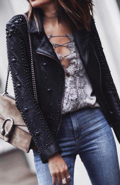 Läderjacka med svarta dubbar och blå jeans