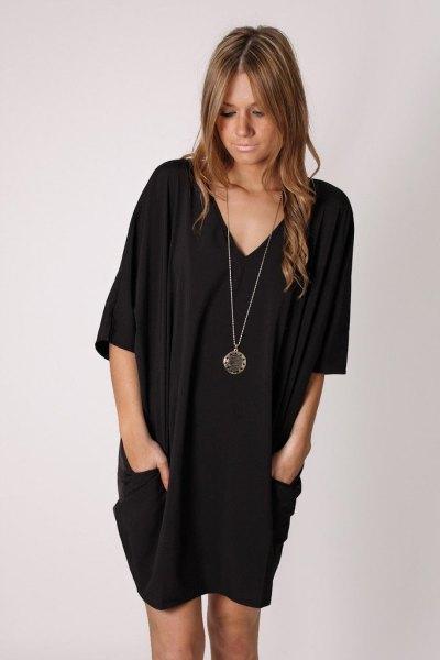 svart tunikaklänning med V-ringning och långt halsband