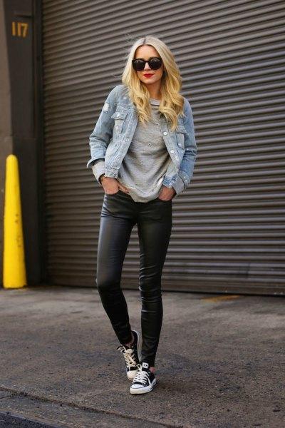 blå jeansjacka med svarta leggings och sneakers i canvas