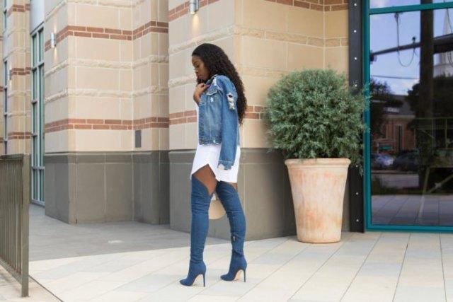 blå jeansjacka med vit miniklänning och högklackade denimstövlar