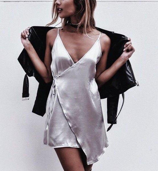 vit sidenklänning med djup V-ringning och skinnjacka