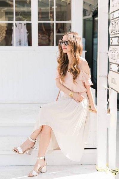 Ljusrosa chiffongblus med maxi vit veckad kjol och gyllene klackar med öppen tå
