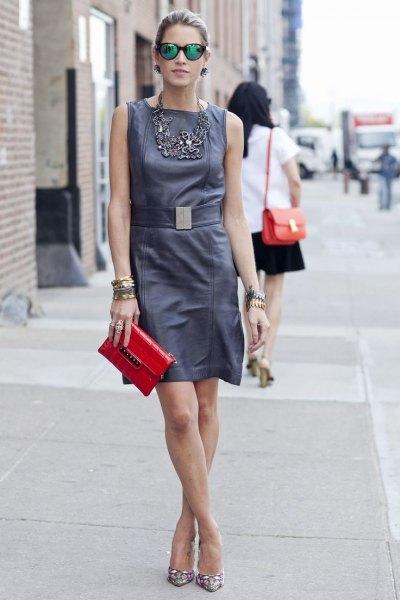 grå miniklänning med samlad midja och röd läderhandväska