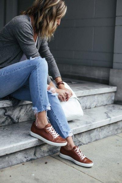 grå t-shirt med ljusblå jeans med smal passform och bruna läderskor