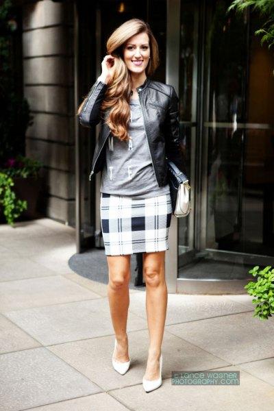 svart läderjacka med grå långärmad grafisk t-shirt och rutig pennkjol