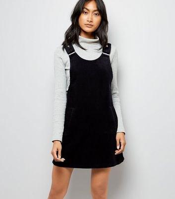 ljusgrå mock neck tröja med svart hängslen klänning