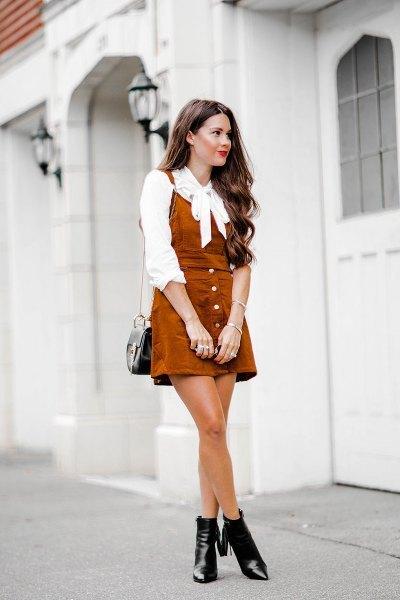 vit fluga-blus med brun miniklänning och läderstövlar