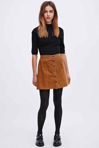 svart mock-neck tröja med halva ärmar och brun corduroy mini kjol