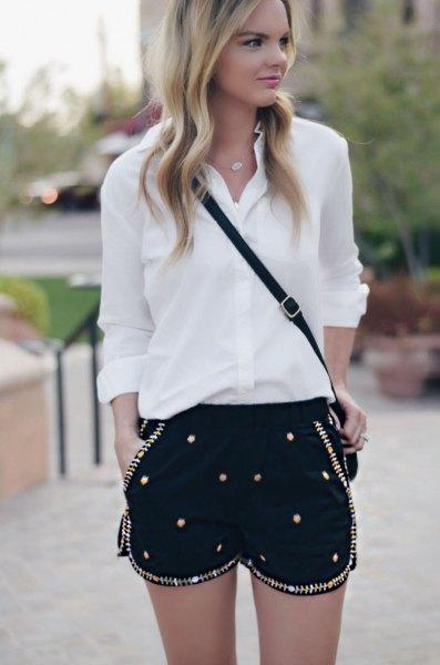 vit chiffongskjorta med knapplås, svarta shorts broderade med paljetter