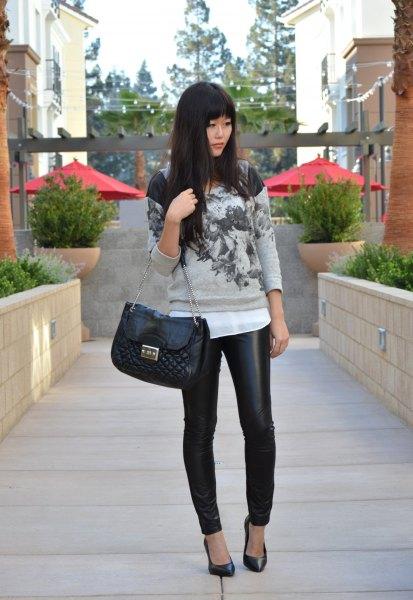 grå tröja med vit chiffongblus och quiltad plånbok i svart läder