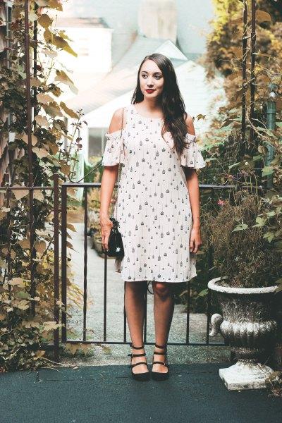 vit, knälång klänning med kallt axelmönster och svart läderhandväska