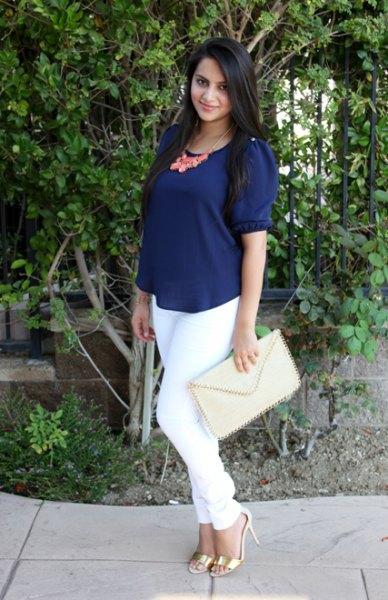 Mörkblå kortärmad blus med scoop-halsringning och vita smala jeans