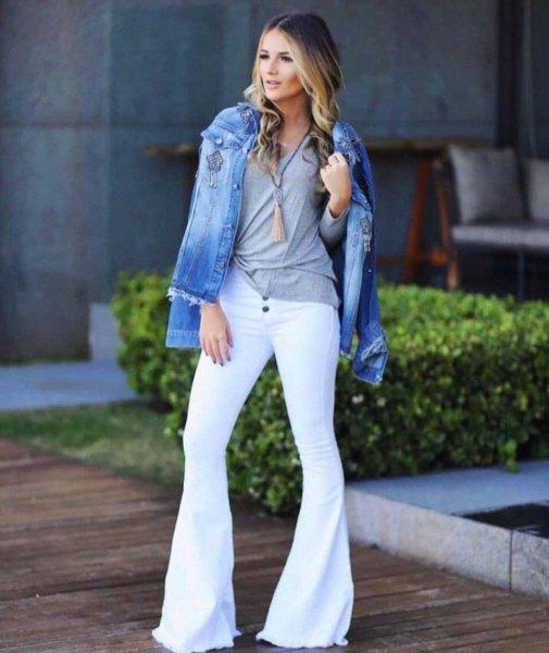 blå jeansjacka med grå t-shirt och vita jeans med klockbotten