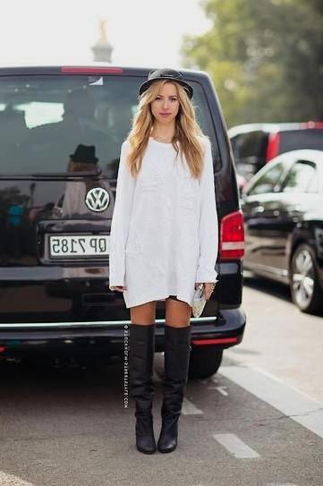 vit långärmad klänning med svart filthatt och läderstövlar
