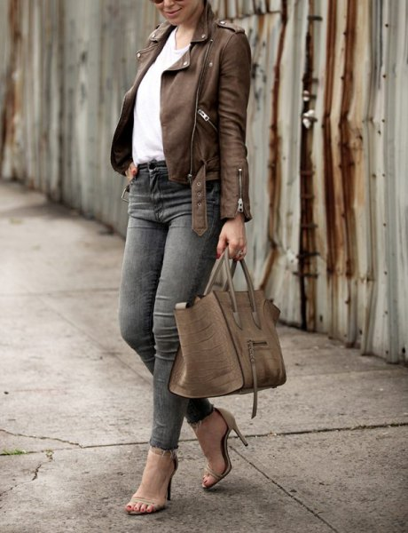 brun läderjacka med vit blus och grå skinny jeans