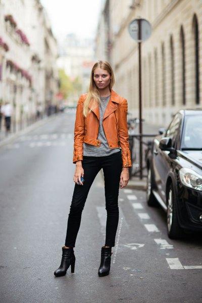 orange-brun läderjacka med grå t-shirt och svarta jeans