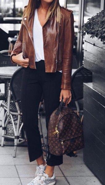Läderjacka med en vit blus med en urringning och korta svarta byxor