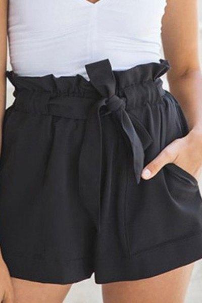 vit, ärmlös blus med V-ringning och svarta minishorts