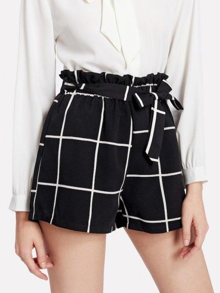 vit blus med knappar och svarta rutiga shorts