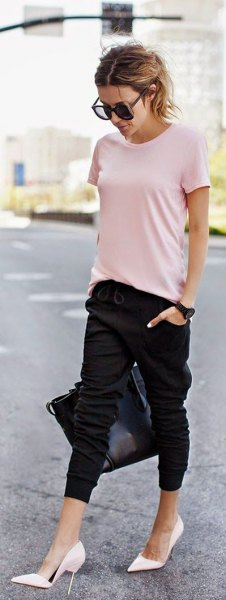 Ljusrosa t-shirt med svarta byxor och vita höga klackar
