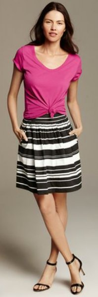 rosa knuten t-shirt med scoop halsringning och svart och vit randig knälång kjol