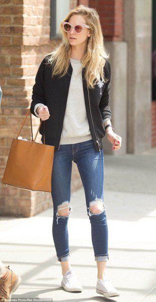 Ljusgrå tröja med rund hals, svart flygjacka i läder och rippade jeans